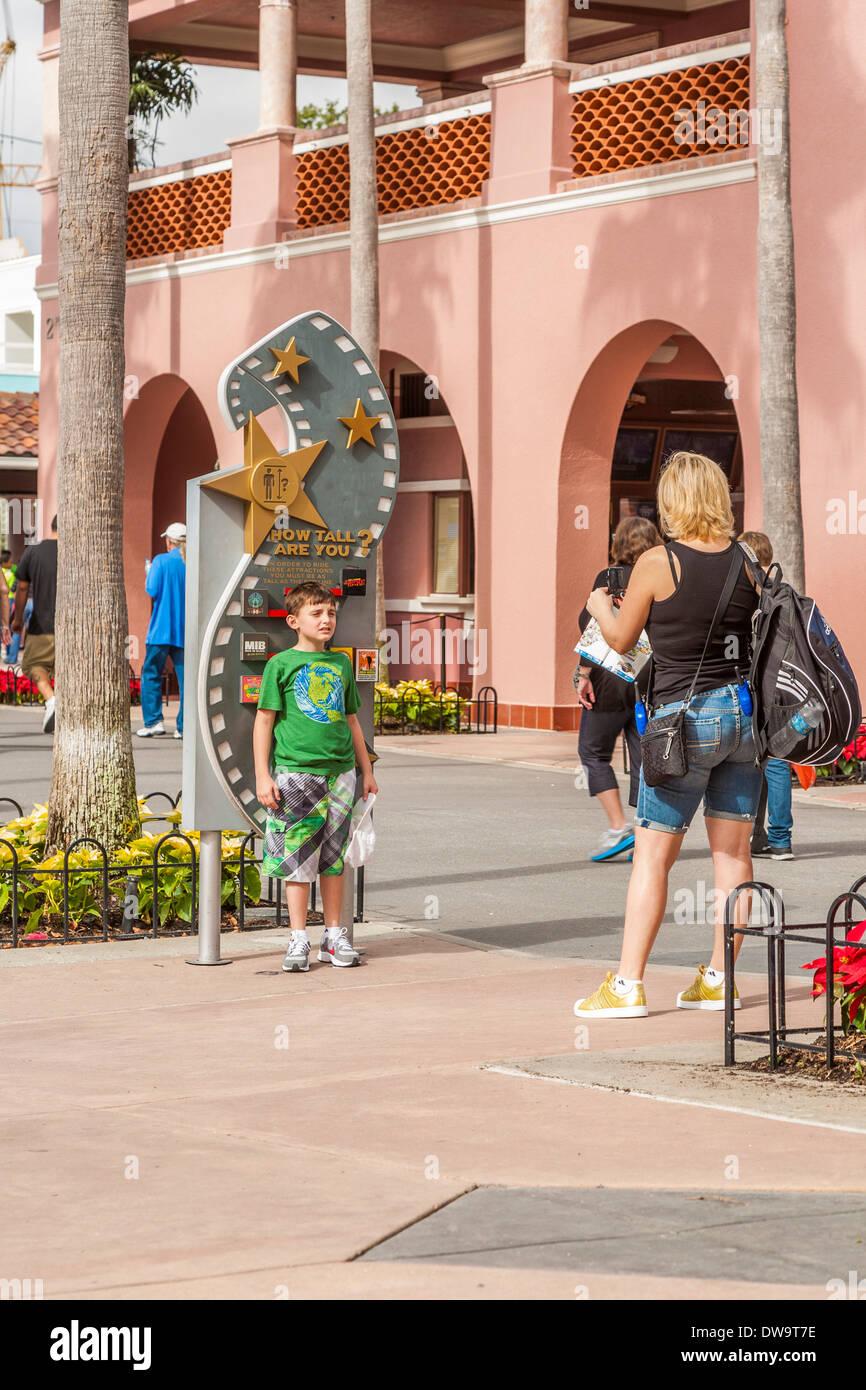 Mère prend photo de fils en hauteur graphique près de l'entrée de parc à thème Universal Studios à Orlando, Floride Photo Stock