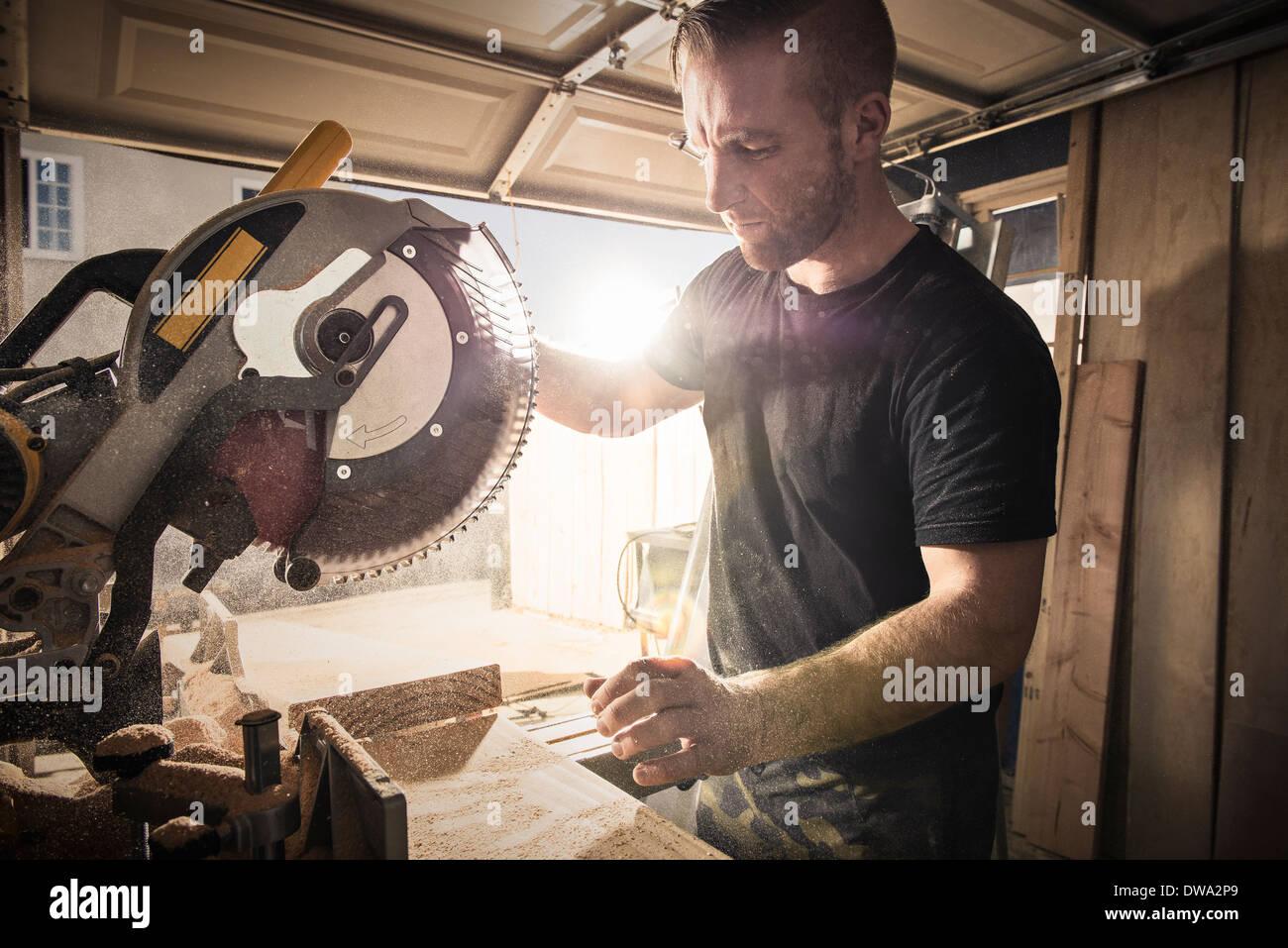 Male carpenter travailler avec une scie rotative en atelier Photo Stock