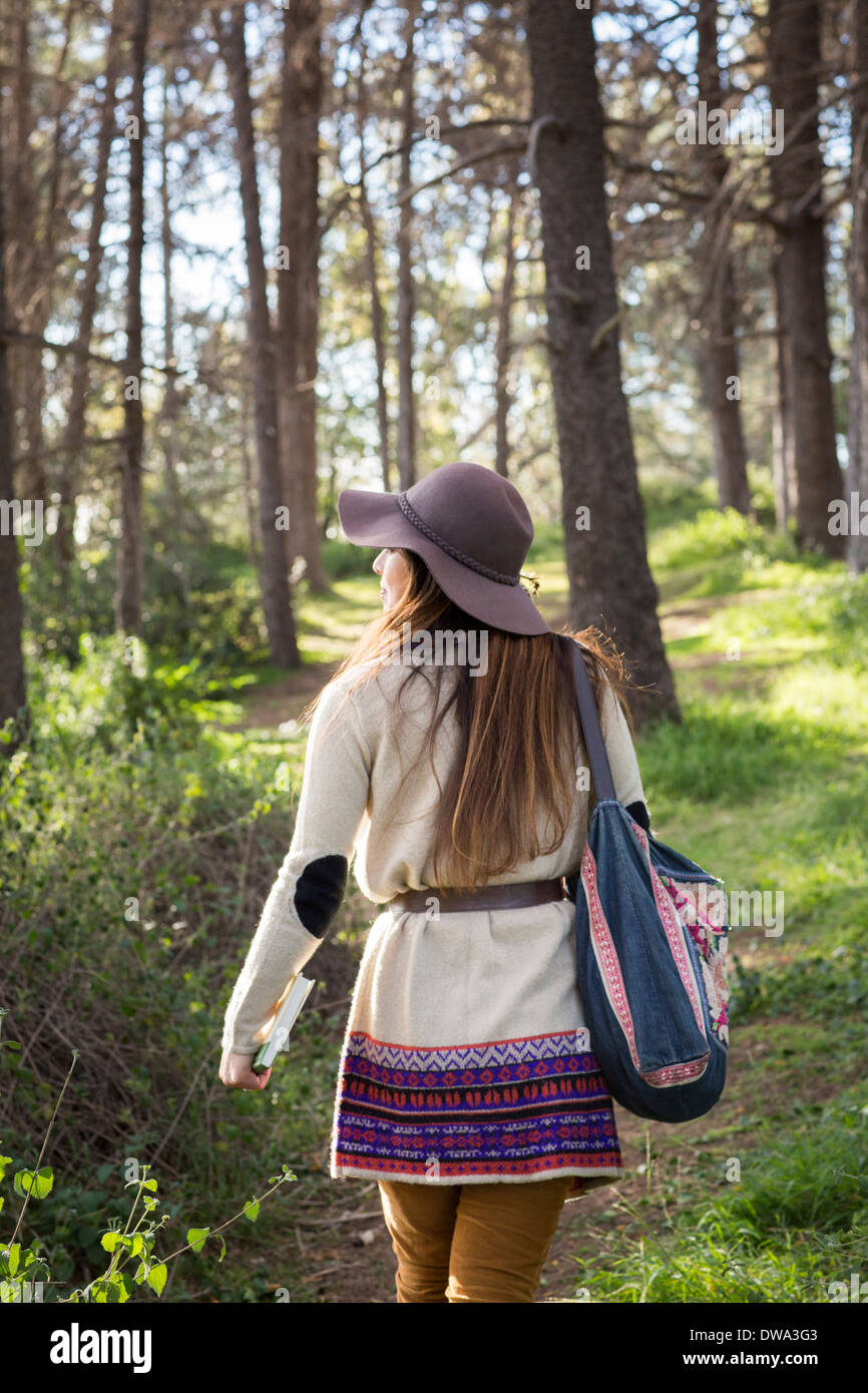 Young woman wearing hat in forest Photo Stock