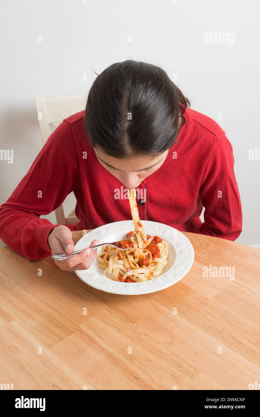 Teenage girl eating pasta Banque D'Images