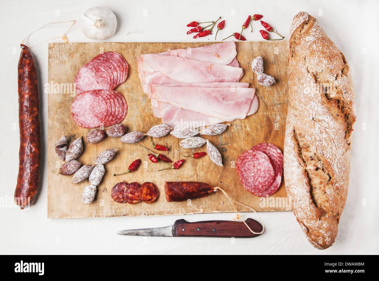 Ensemble de salami et de jambon servi avec du pain frais sur la vieille planche à découper en bois. Banque D'Images