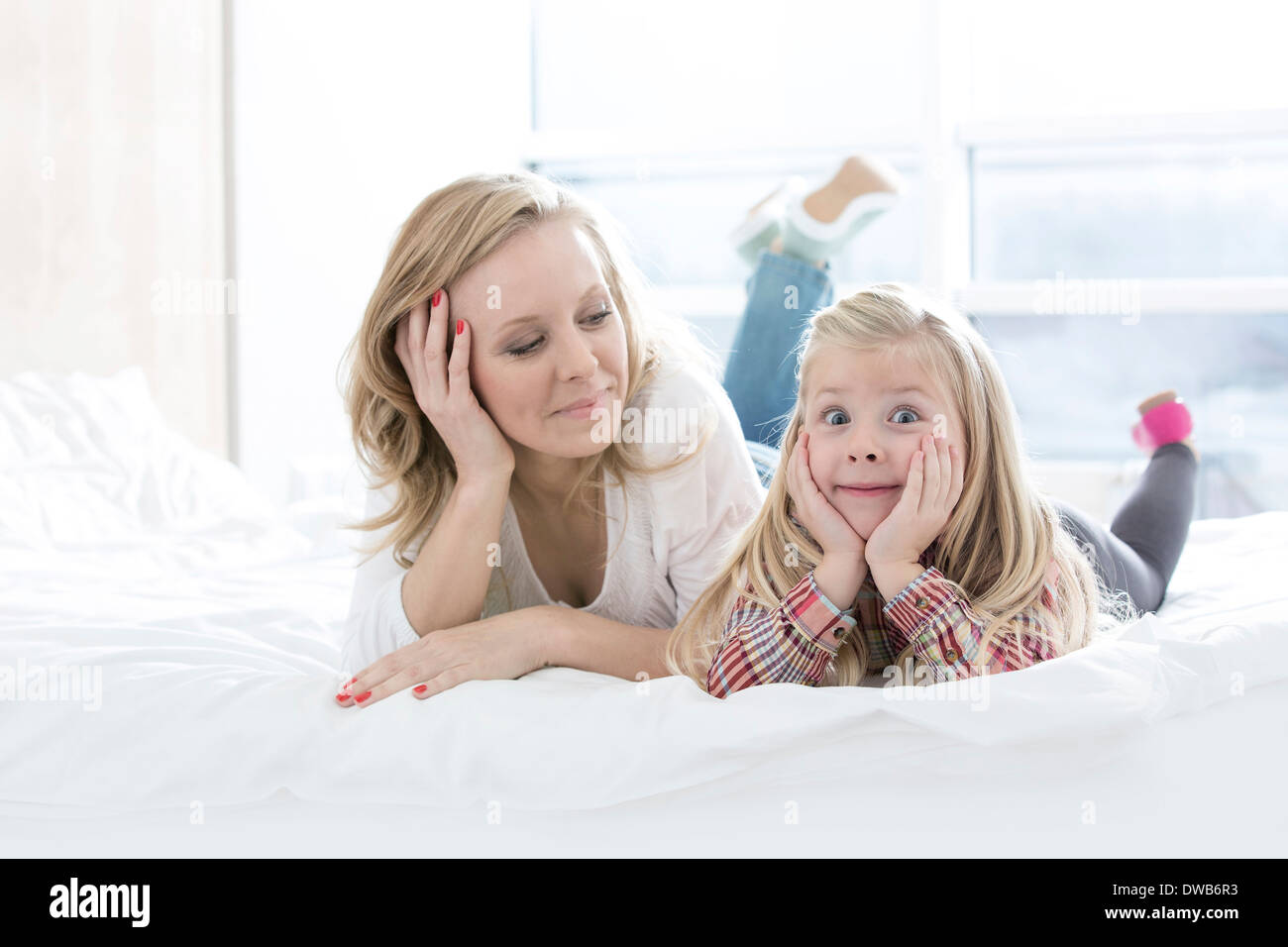 Mère regardant cute fille making faces while Lying in Bed Photo Stock