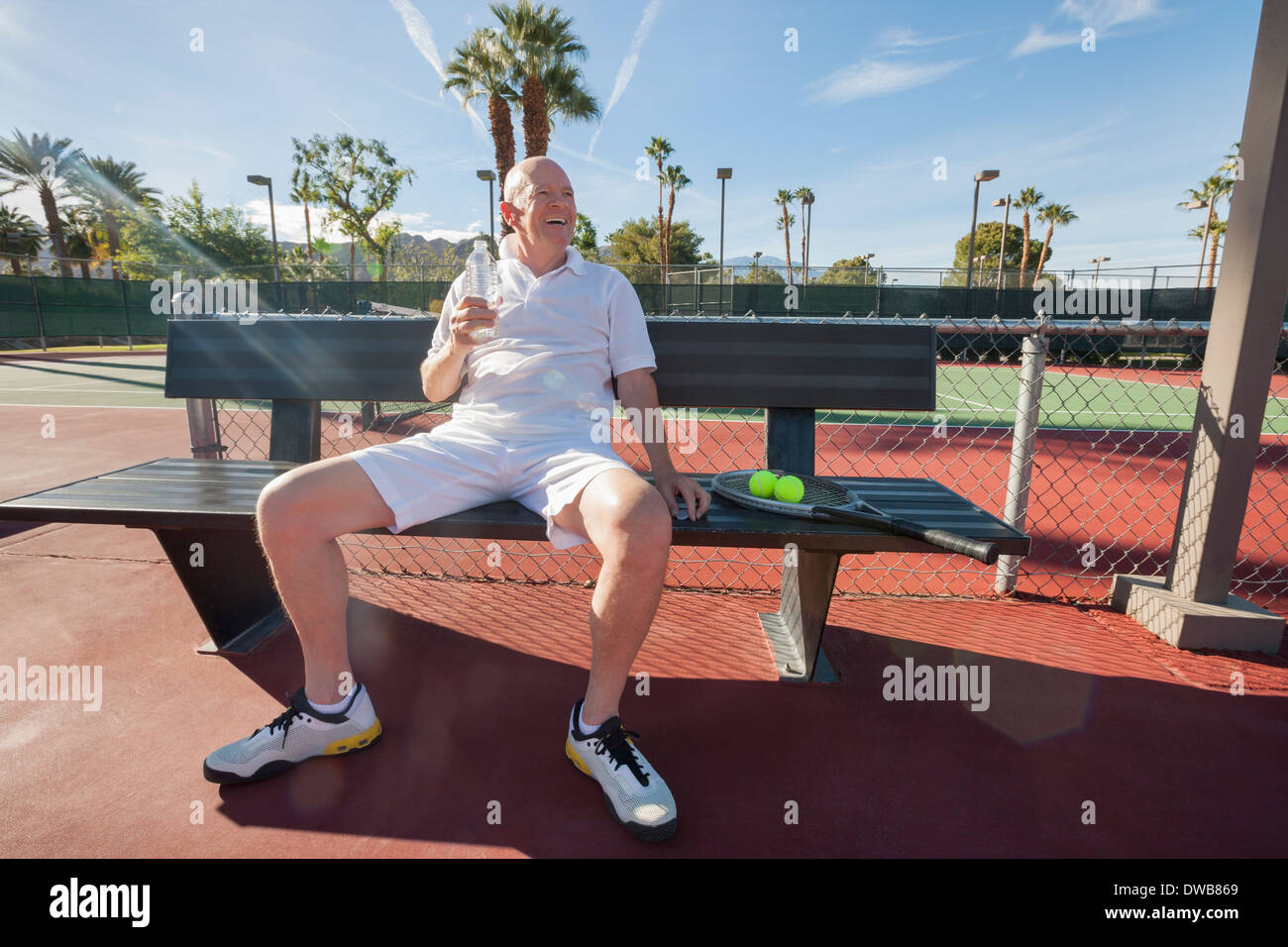 Happy senior male tennis player avec bouteille de l'eau assis sur un banc à la cour Photo Stock