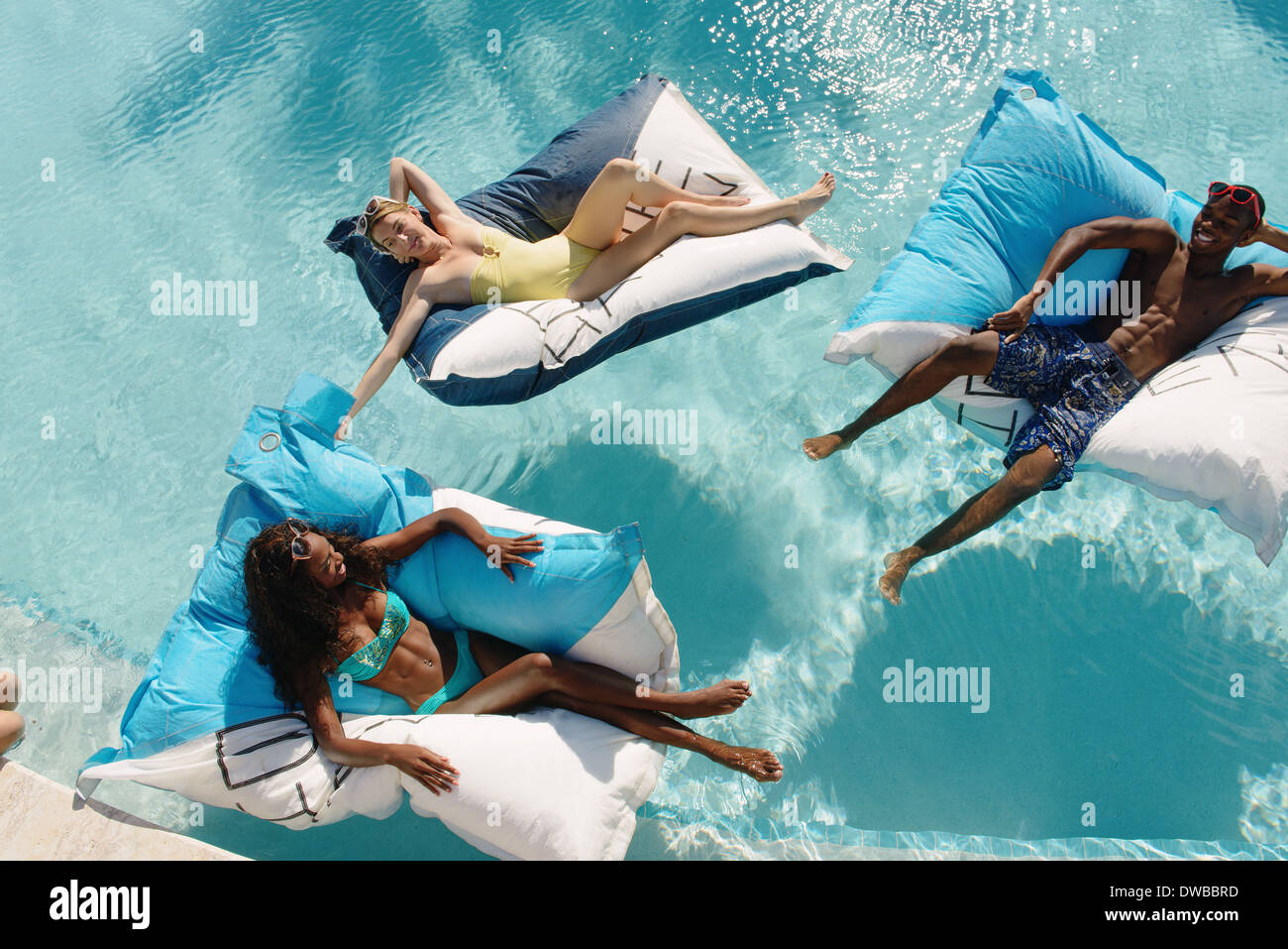Trois jeunes adultes couchée sur lits de piscine, Providenciales, Turks and Caicos Islands, Caribbean Photo Stock