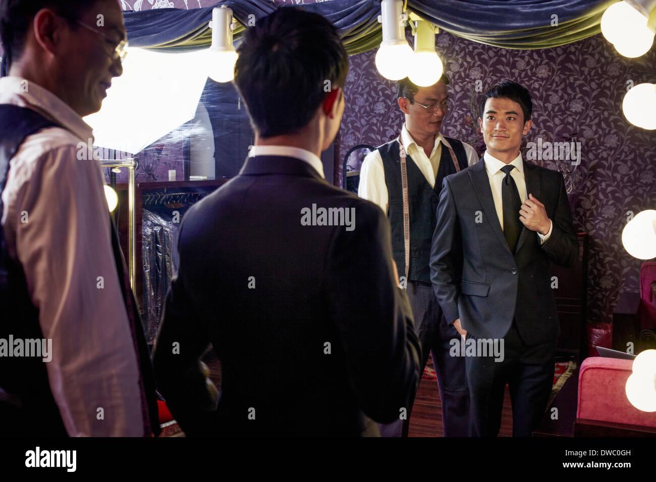Solutions sur mesure avec les jeunes clients masculins essayant sur nouveau costume dans shop Photo Stock