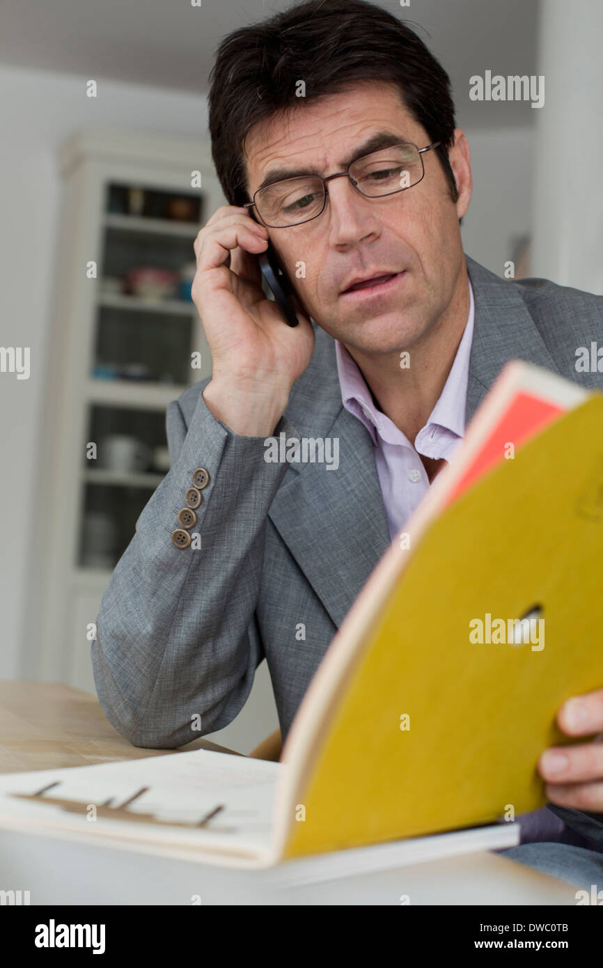 Man working at home using mobile phone Banque D'Images