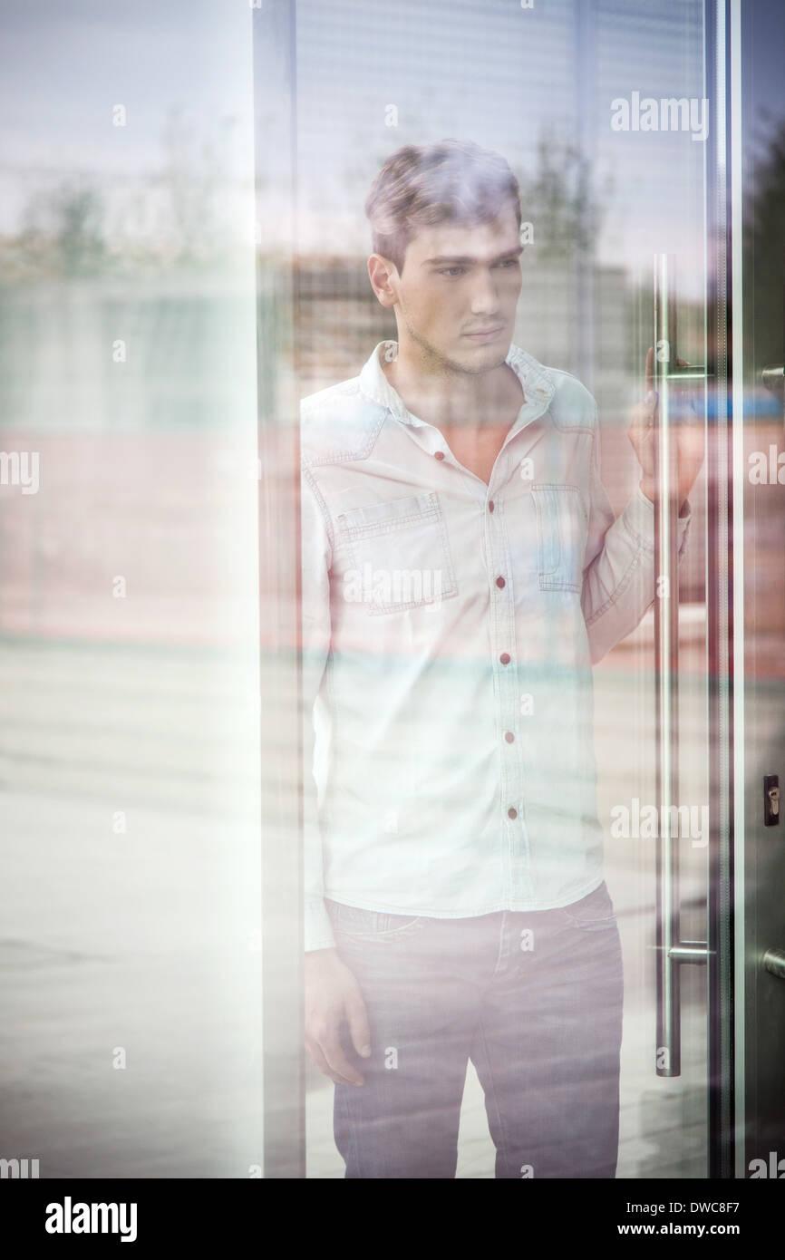 Malheureux jeune homme derrière la fenêtre réfléchissante Photo Stock