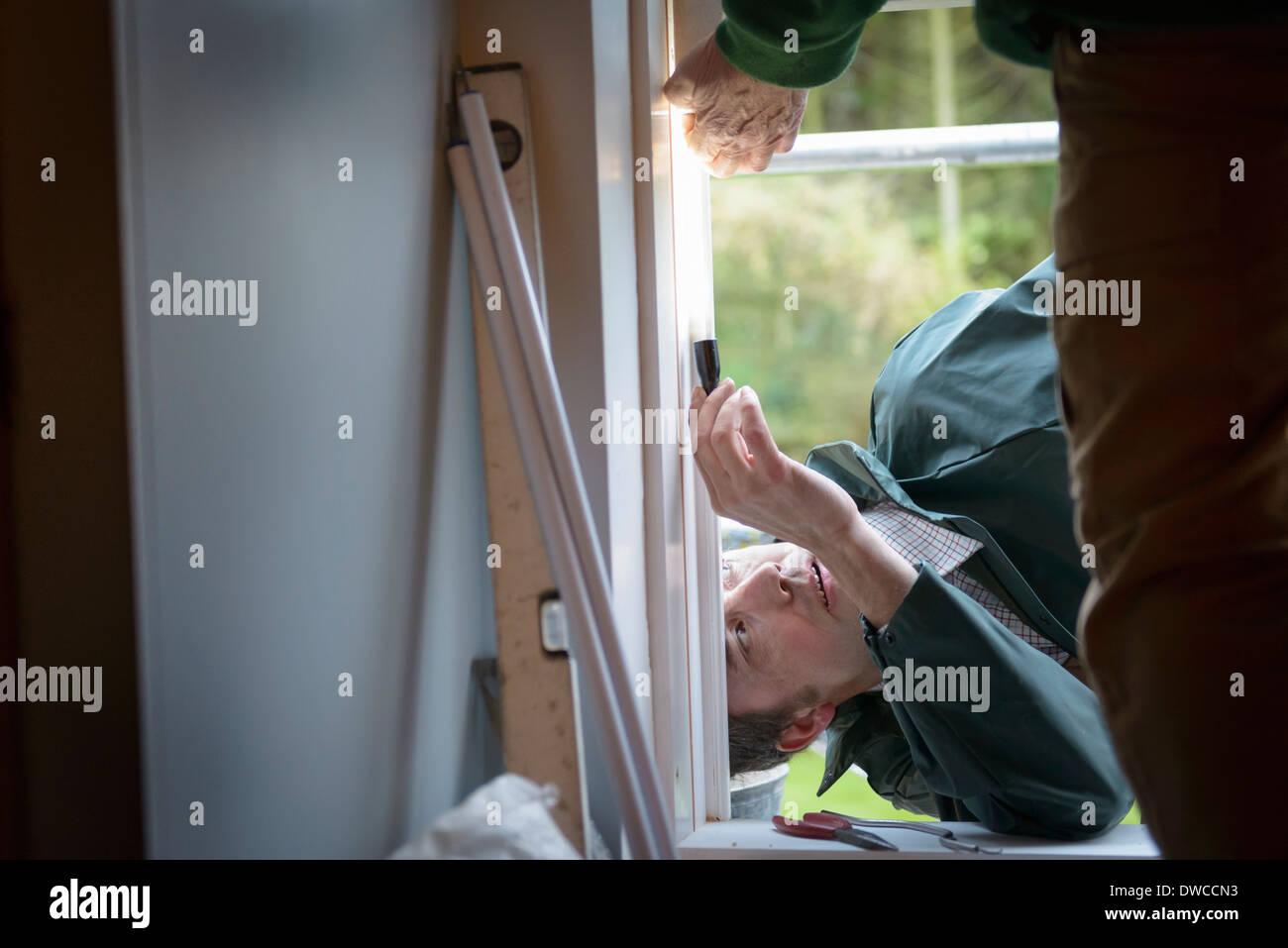 Père et fils builders réglage de nouvelle fenêtre dans la chambre, Close up Photo Stock