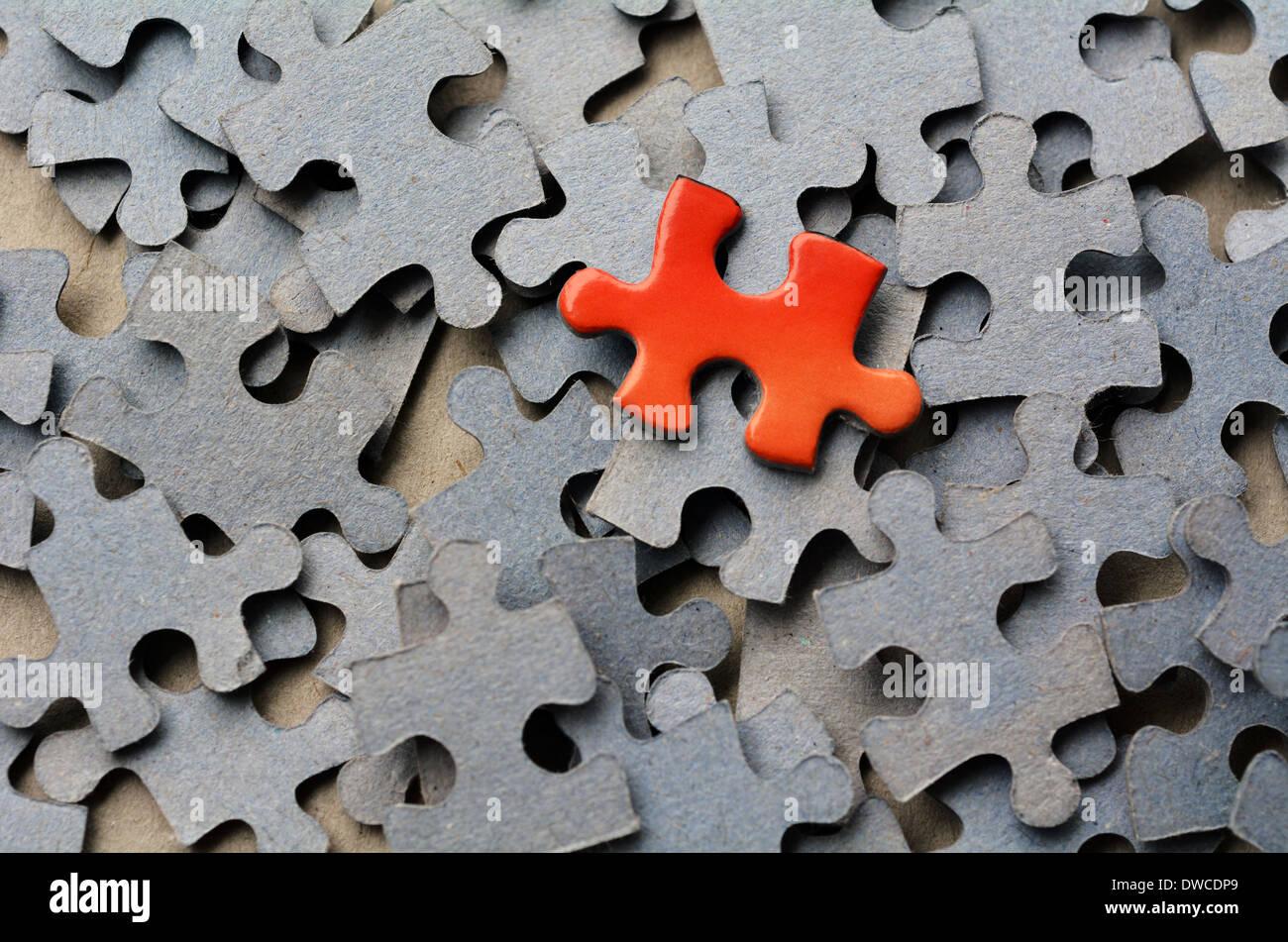 Pièce de puzzle orange se démarquer de groupe plus important des pièces de puzzle. Concept d'affaires - branding, différente, originale. Photo Stock