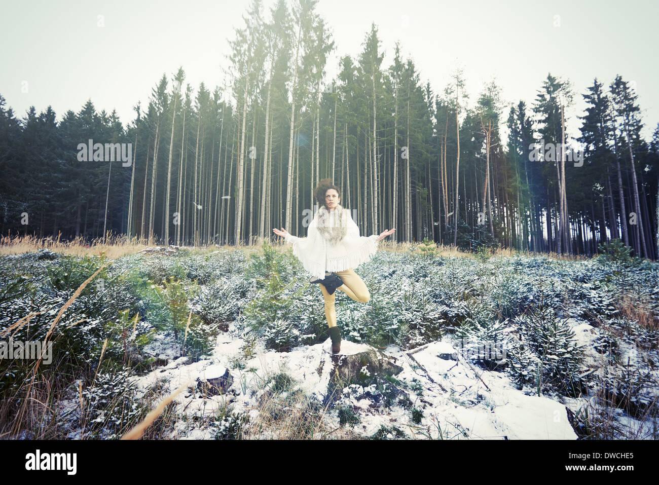 Mid adult woman practicing yoga l'arbre sur pied en forêt Photo Stock