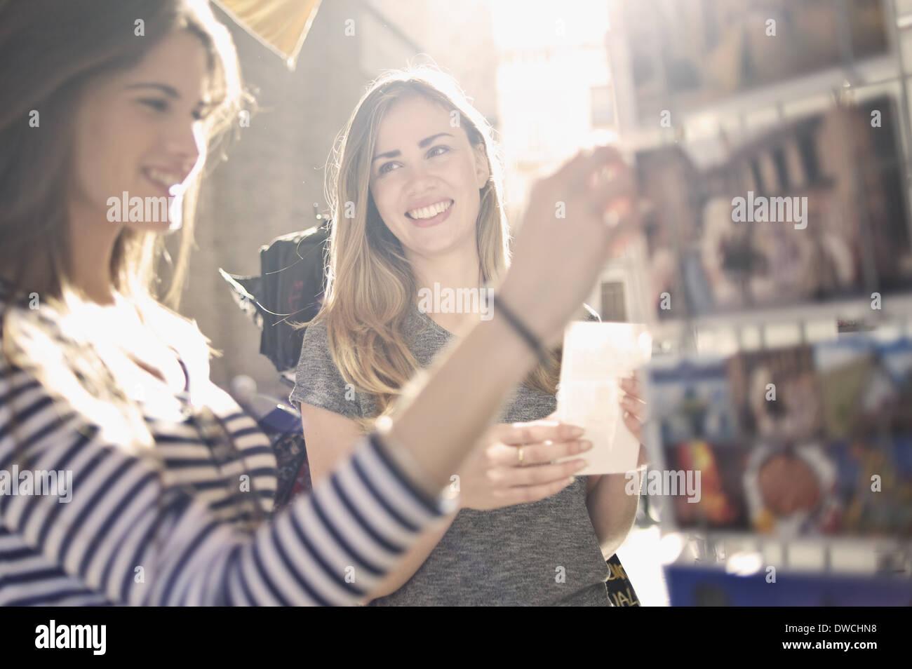 Deux jeunes femmes à la recherche d'amis à cartes postales, Valencia, Espagne Photo Stock