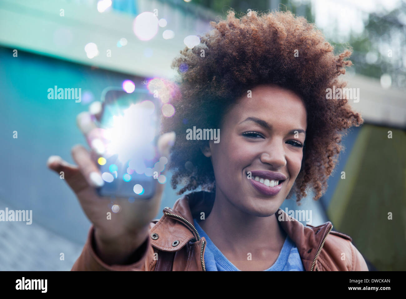 Young woman holding up smartphone avec feux lumineux sortant Photo Stock