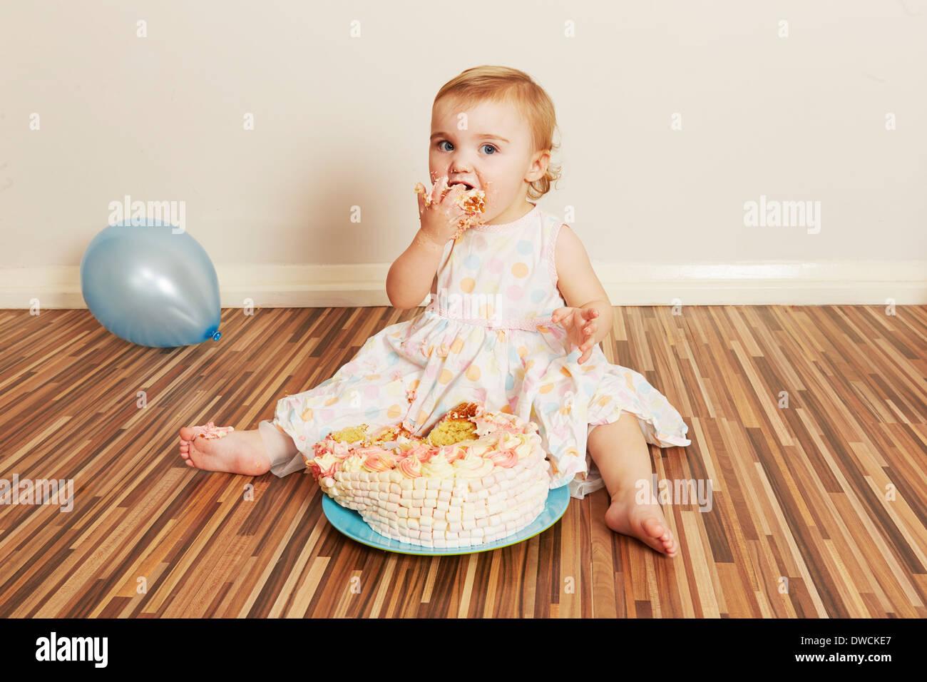 Bébé fille de dévorer le gâteau d'anniversaire Banque D'Images