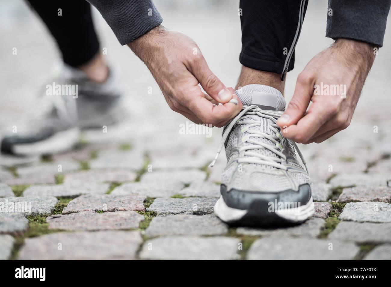 La section basse de l'homme attachant dentelle de la chaussure de sport Photo Stock