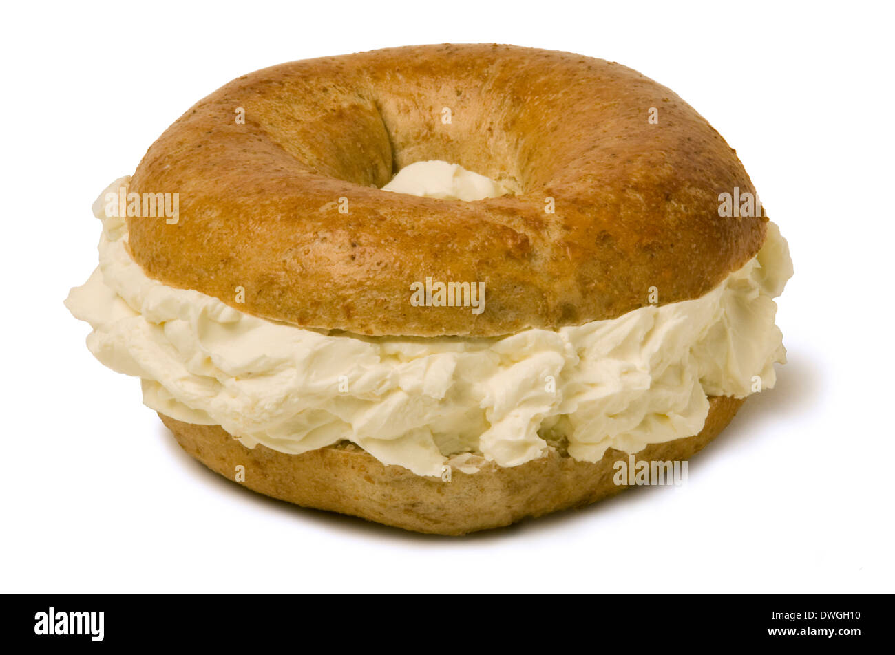 Bagel de blé entier rempli d'une quantité généreuse de fromage à la crème Photo Stock