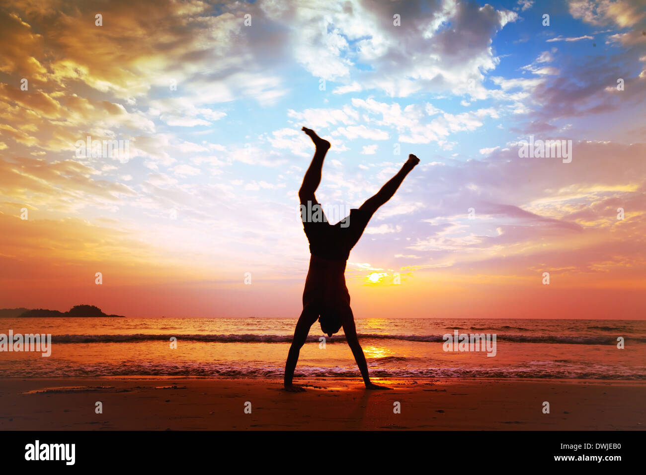 La liberté et la créativité, l'homme sautant sur la plage Photo Stock