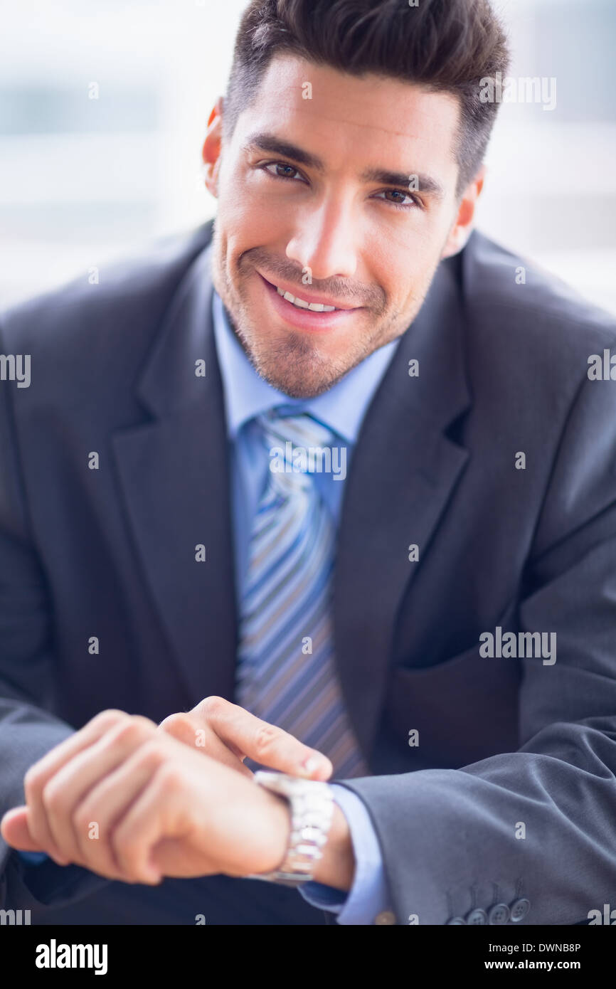 A contrôler sa montre smiling at camera Photo Stock