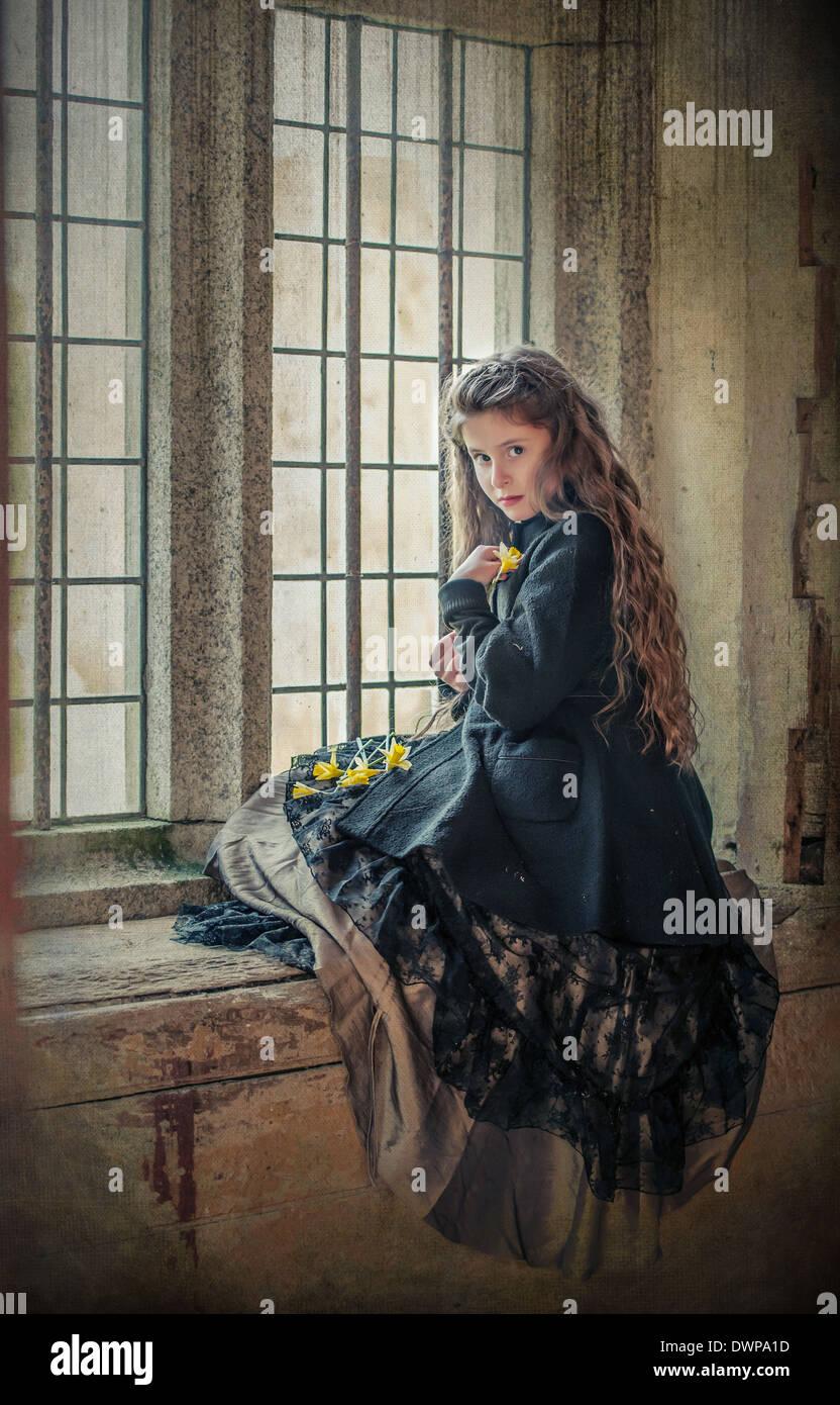 Victorian girl de jonquilles au printemps assis sur le rebord de la fenêtre dans un vieux bâtiment Photo Stock