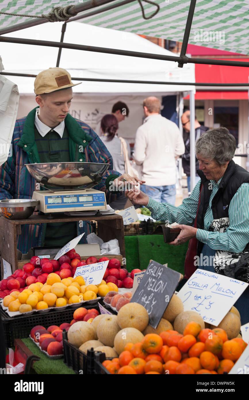 Le paiement du client pour des achats sur l'étal de fruits et légumes. Photo Stock