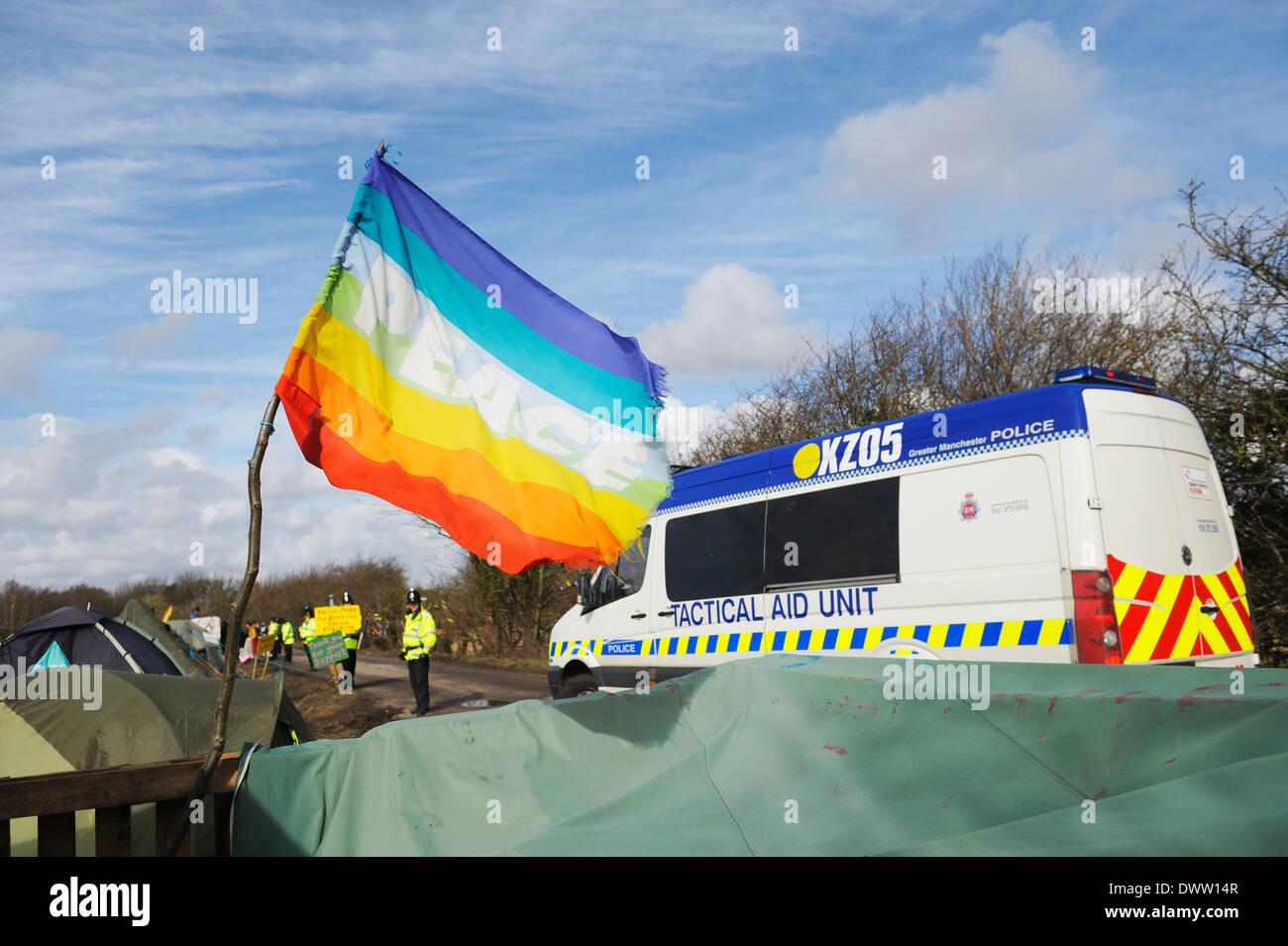 Unité de l'aide tactique pendant la conduite passé un drapeau de paix puisqu'elle conduit les véhicules et les protestataires à l'iGas site de forage. Photo Stock