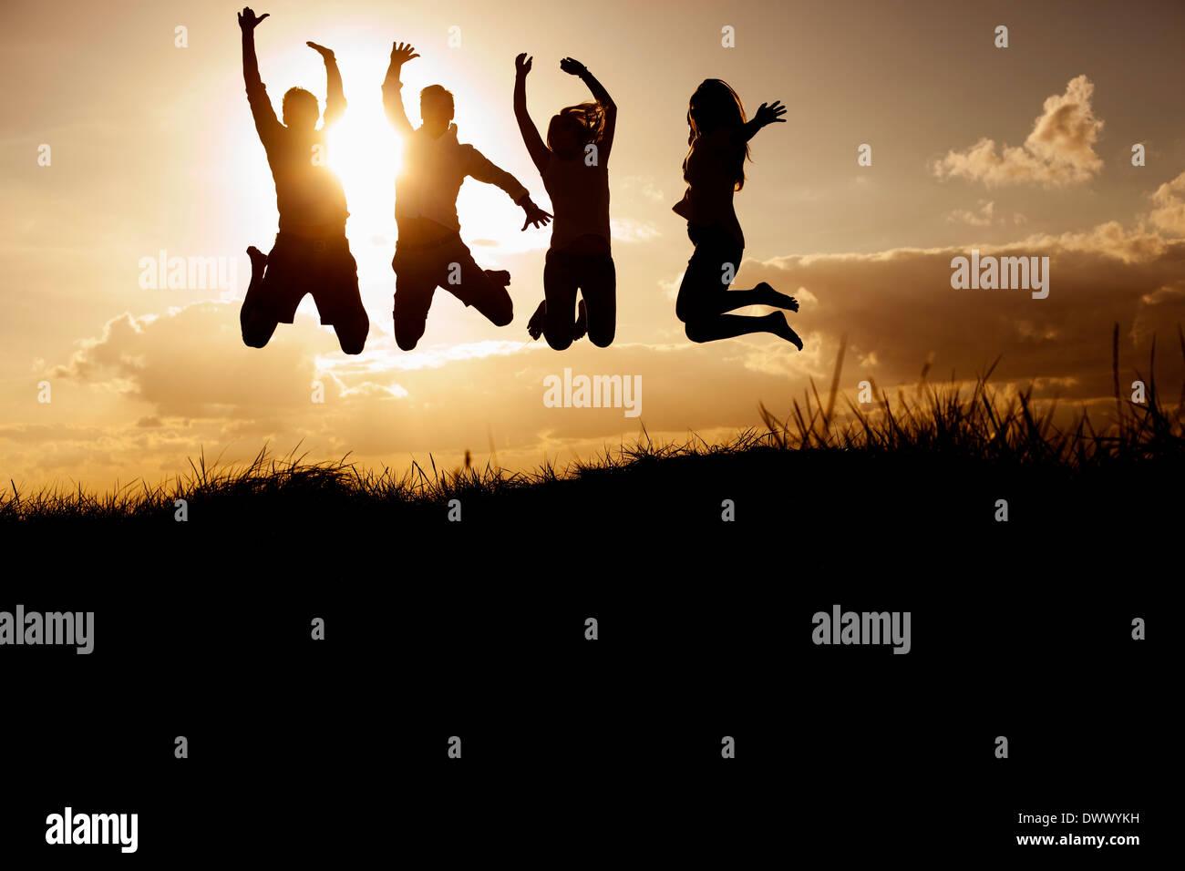 La silhouette du droit d'amis sautant sur beach against sky Photo Stock