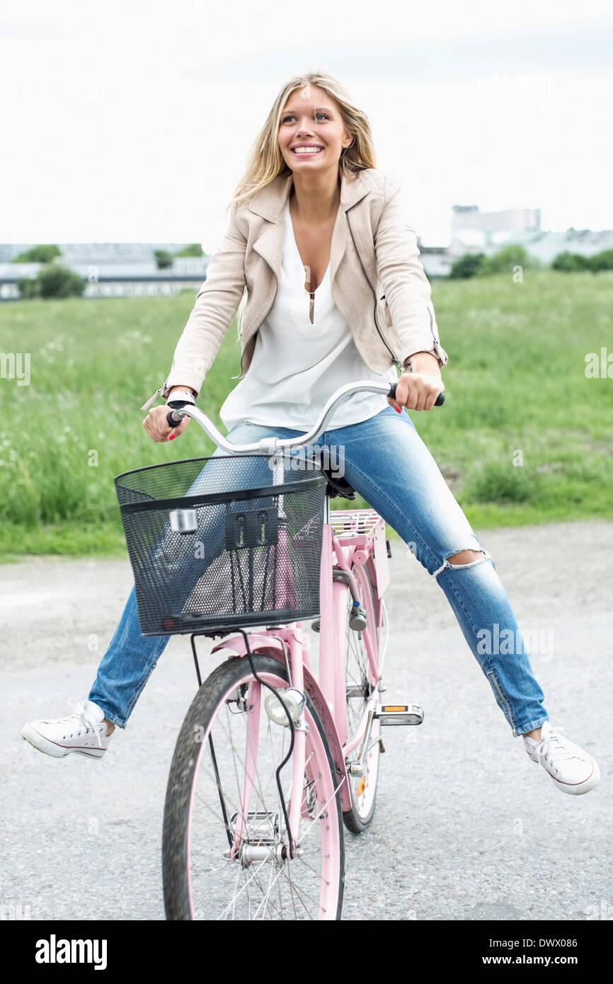 Une jeune femme assise avec les jambes écartées sur vélo à campagne Photo Stock