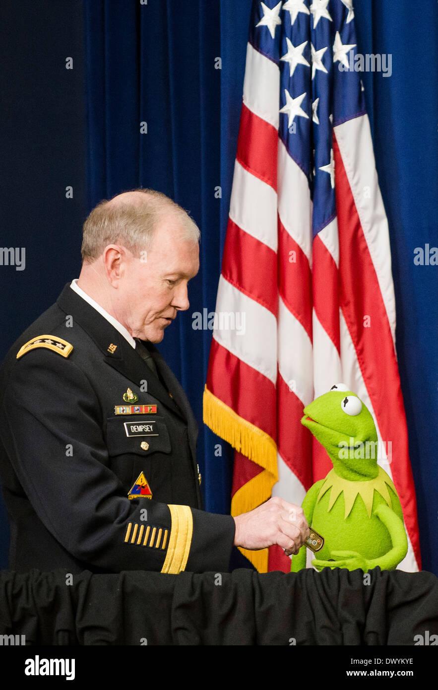 US Joint Chiefs Président Général Martin Dempsey présente Kermit la grenouille avec une pièce de service comme ils se félicitent de familles militaires pour un film projection du nouveau film Les Muppets, 'Muppets Most Wanted', à la Maison Blanche le 12 mars 2014 à Washington, DC. Photo Stock