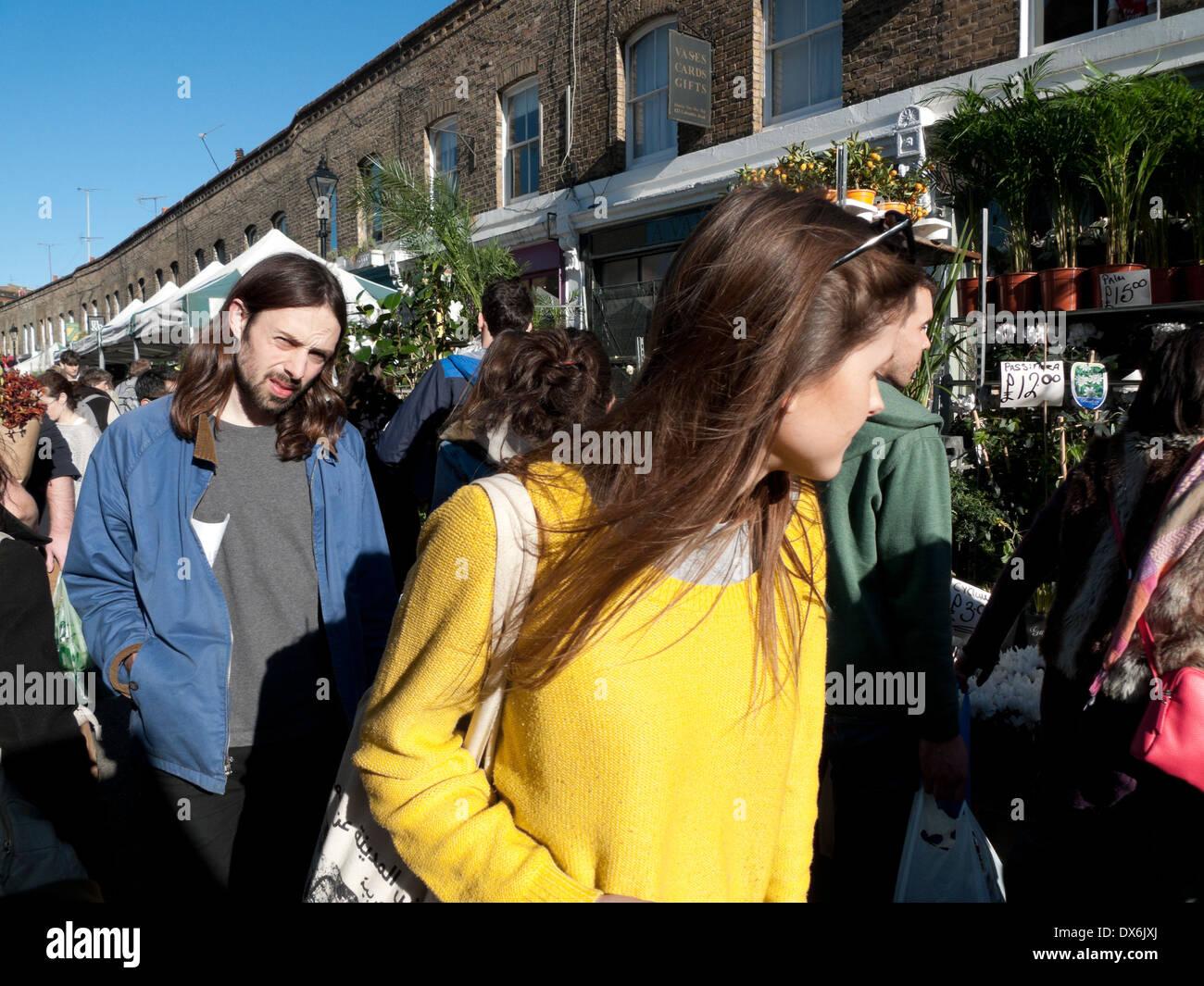 Femme portant cavalier jaune parcourt Columbia Road Flower Market London E2 England UK KATHY DEWITT Photo Stock