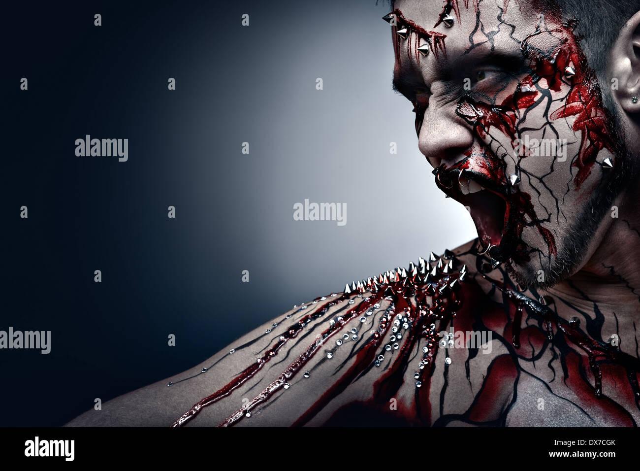 Un concept d'une halloween creepy crier moor dans la douleur avec un piercing et sanglant, l'art corporel. Photo Stock