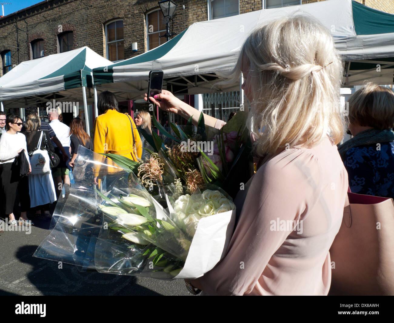Woman holding lilies selfies photographies avec téléphone mobile à Columbia Road Flower Market London E2 UK KATHY DEWITT Photo Stock