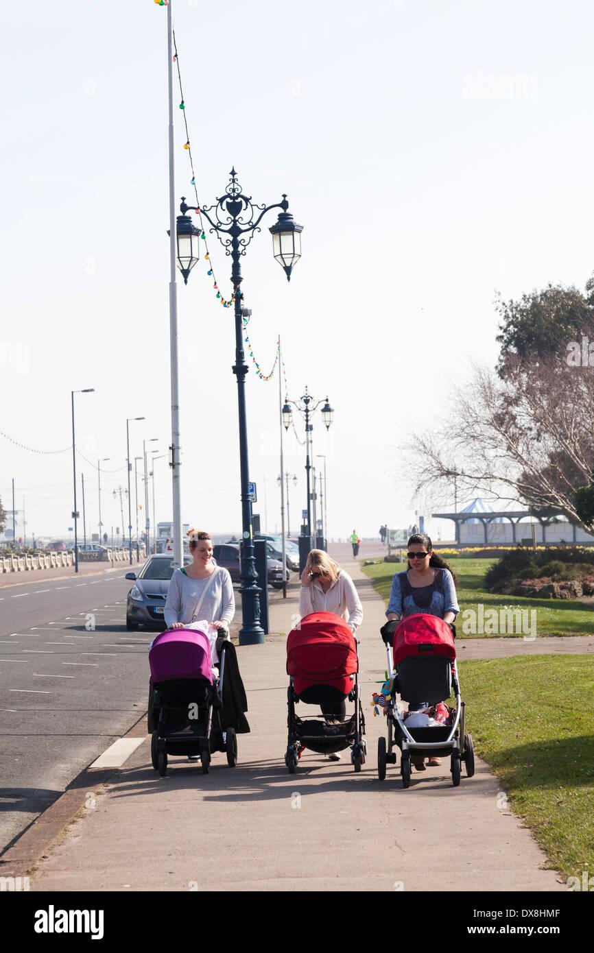 Trois femmes poussant des poussettes de bébé à l'aide de la largeur de la chaussée. Photo Stock