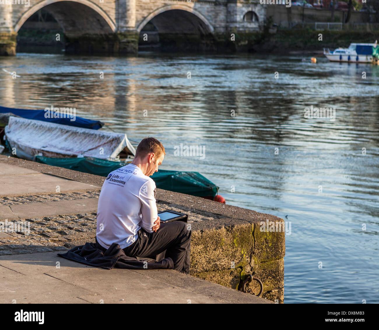 Jeune homme utilise e-reader sur les rives de la Tamise - Richmond upon Thames, London, UK Photo Stock