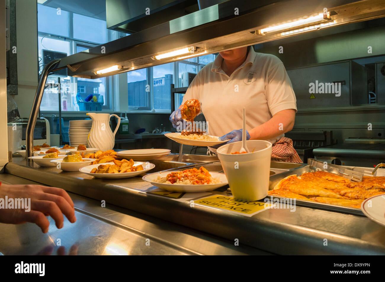 Une femme au travail distribuer des servant de la for Emploi cuisinier cantine scolaire