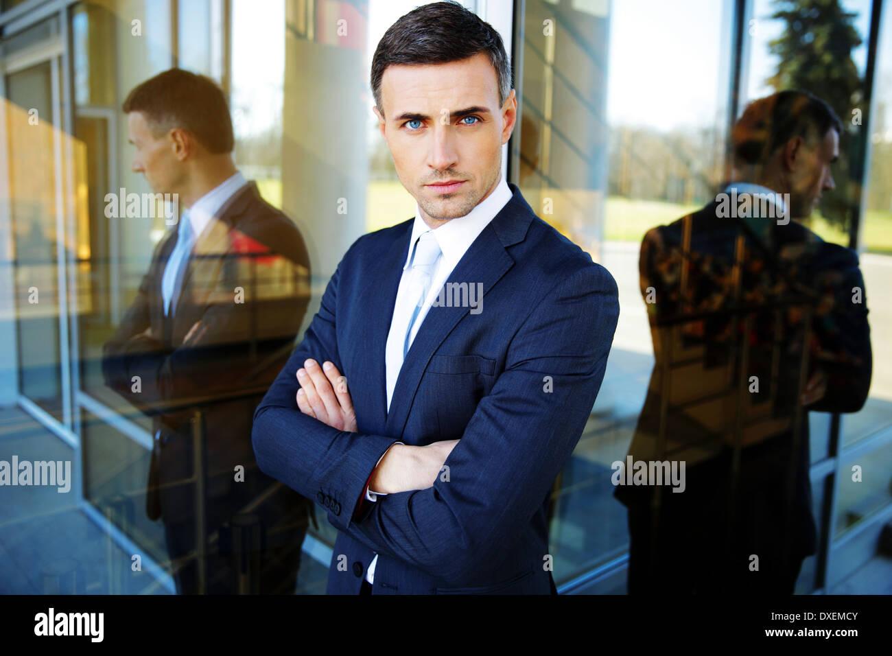 Portrait d'un confident businessman standing with arms folded Photo Stock