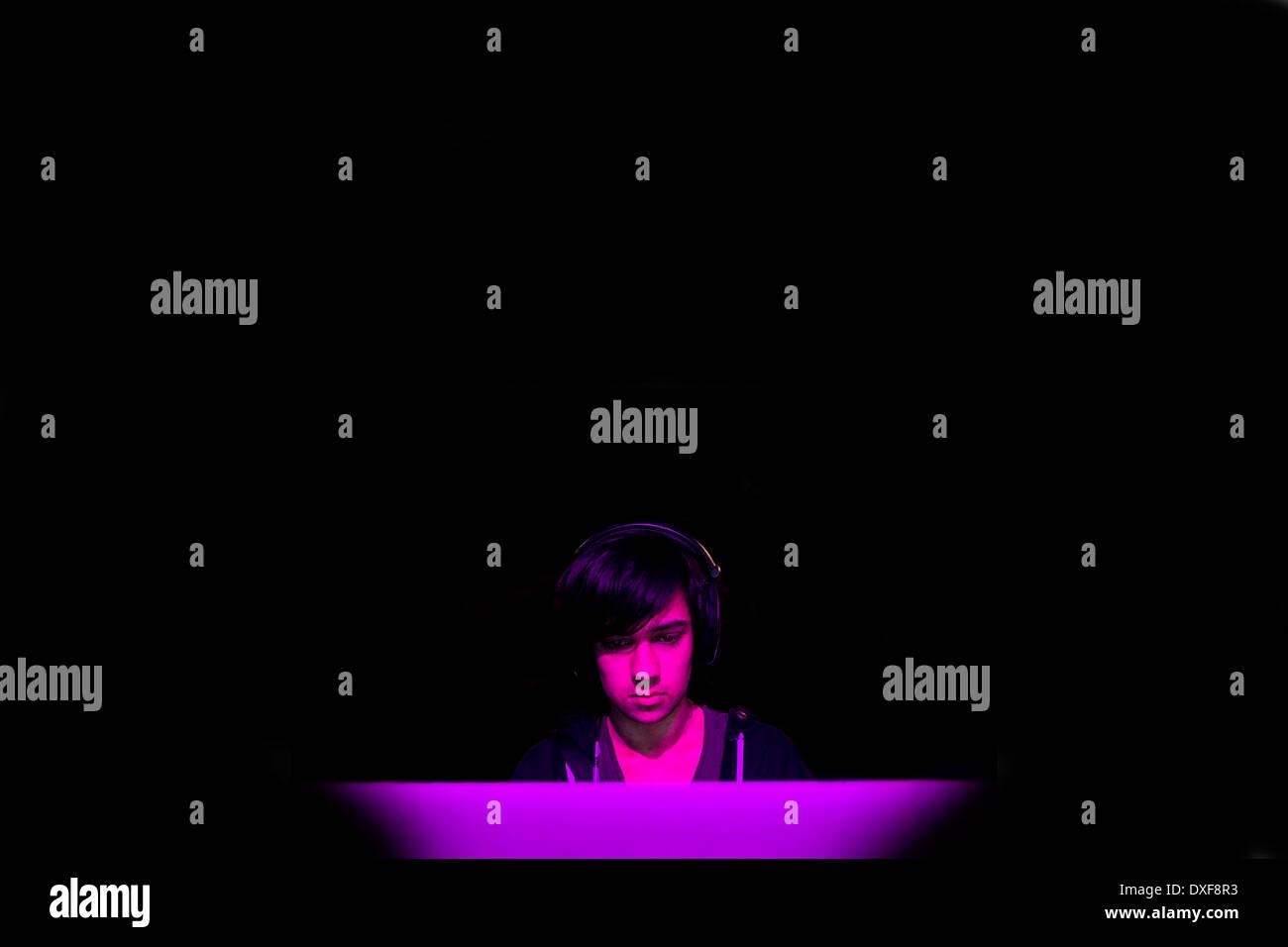 Un adolescent mâle jouant un jeu d'ordinateur dans une pièce sombre. Photo Stock