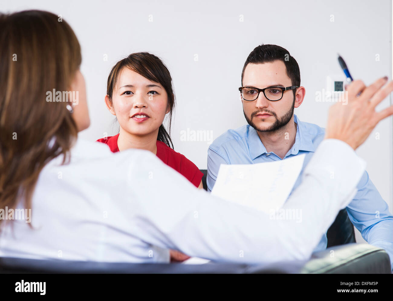 Portrait of boy businesswoman en discussion avec jeune couple, Allemagne Banque D'Images