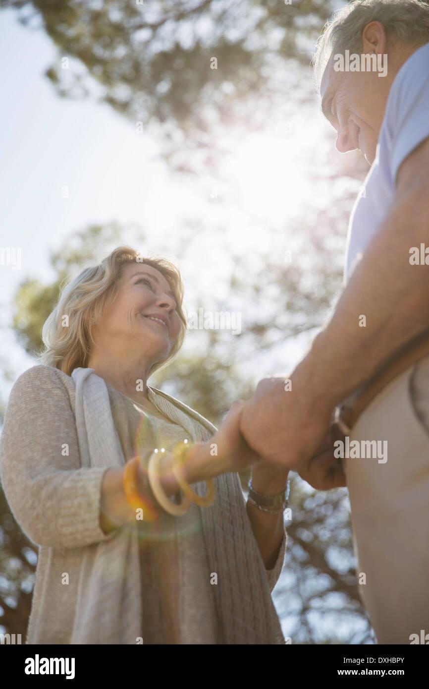 Senior couple holding hands sous les arbres Photo Stock