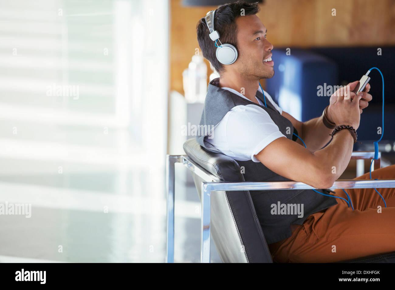 Smiling businessman écouter de la musique sur un lecteur mp3 avec des écouteurs Photo Stock