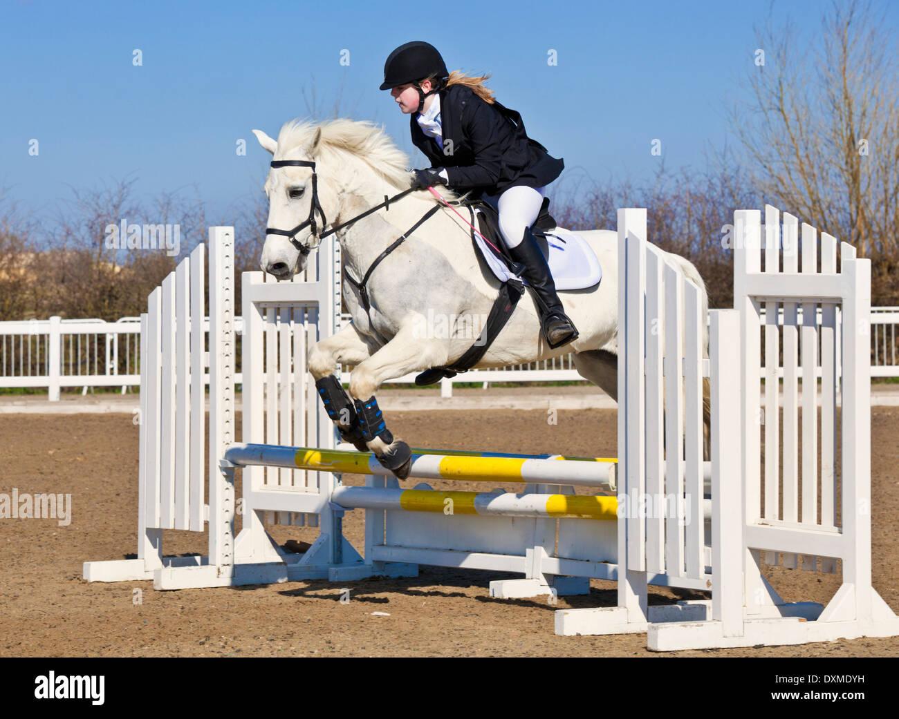 Jeune fille sautant un Cheval poney blanc sur un saut à un événement de saut Photo Stock