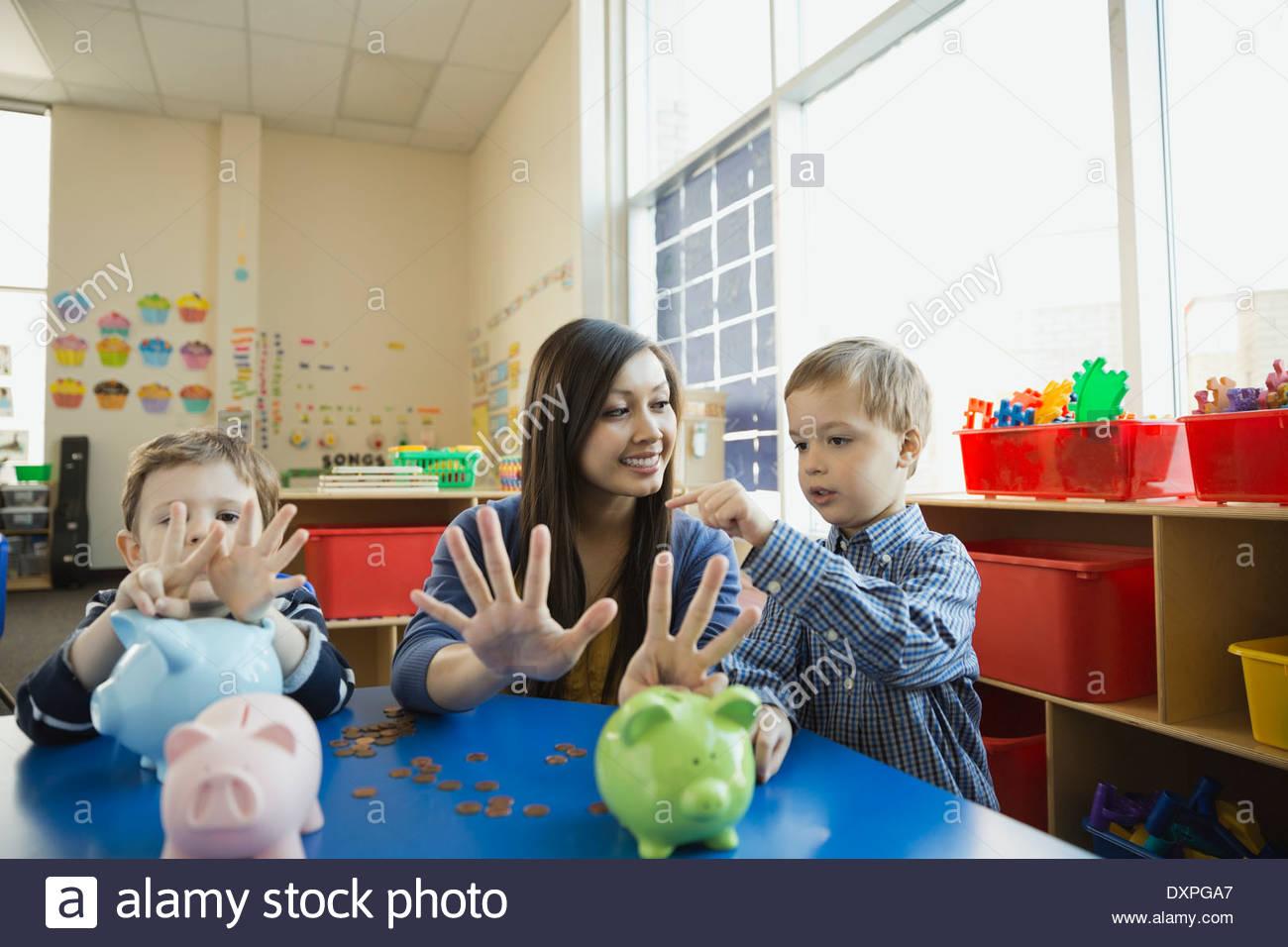 Boy compte sur les doigts des enseignants à l'école Photo Stock