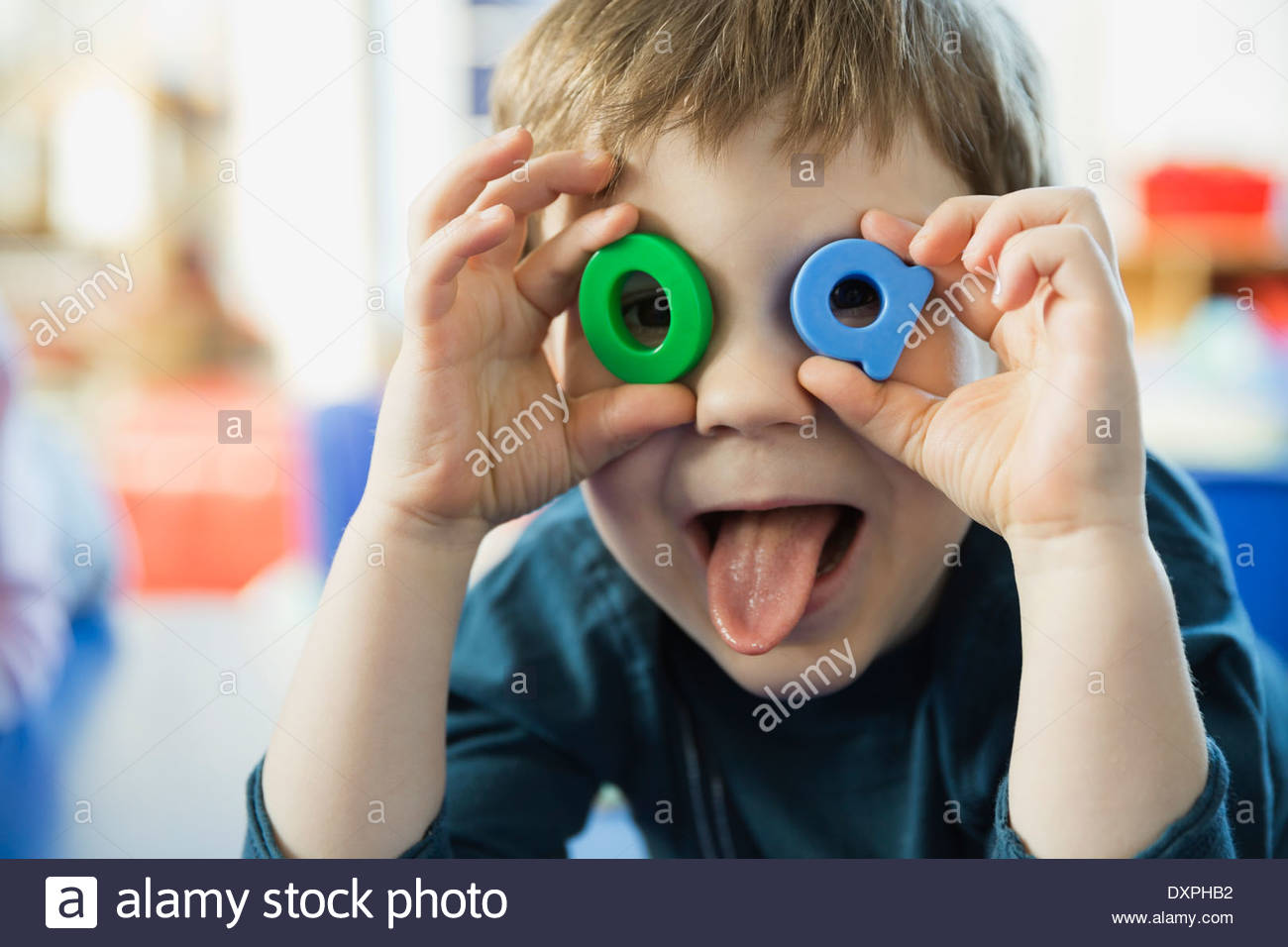 Playful boy making faces avec des lettres Photo Stock