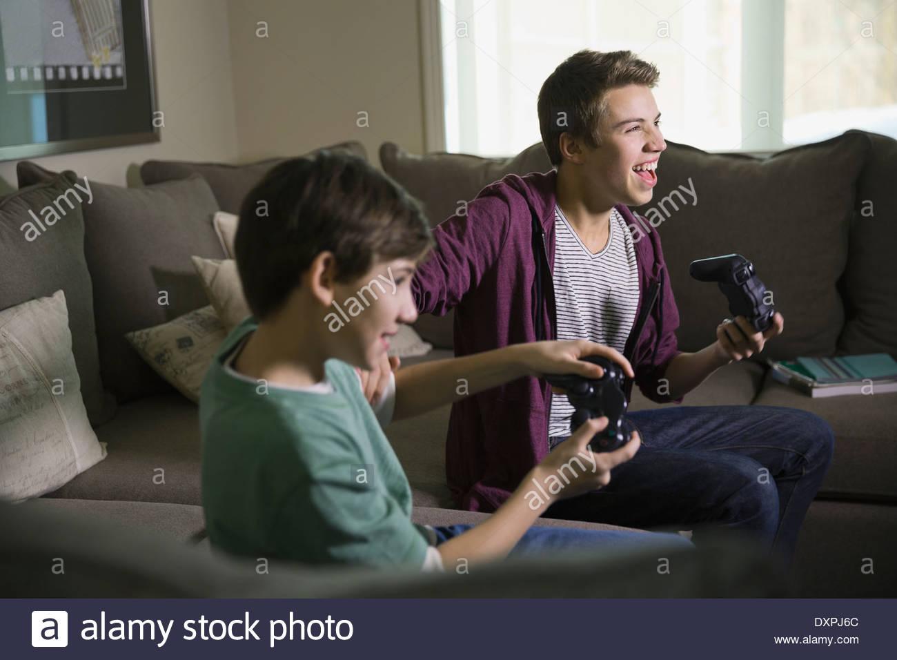 Frères excité à jouer aux jeux vidéo sur canapé Photo Stock