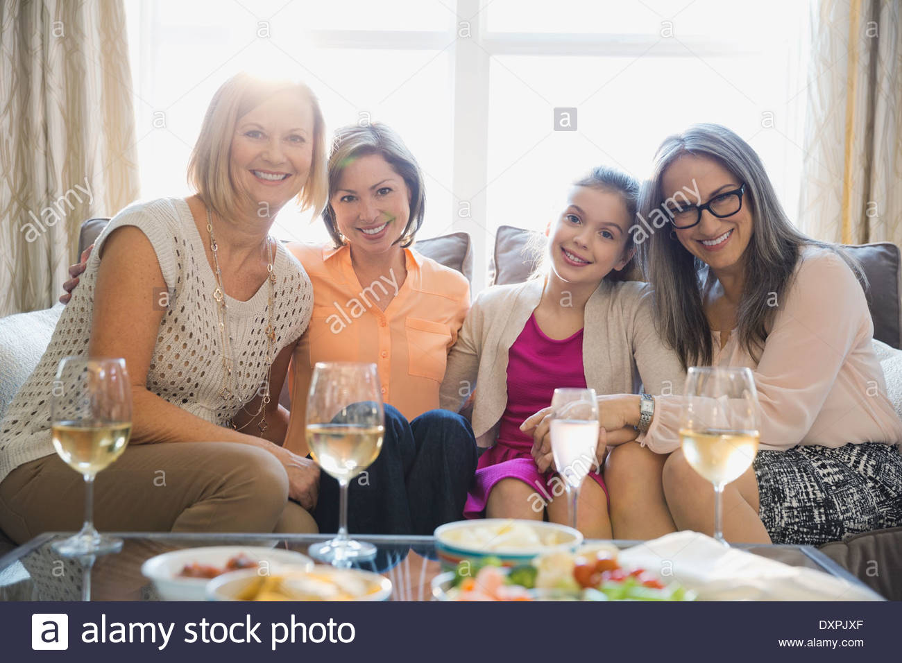 Portrait of smiling femmes assis sur un canapé pendant party Photo Stock