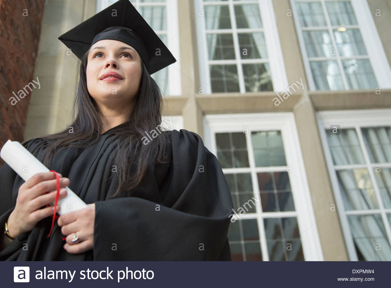 Pensive college graduate holding diploma Photo Stock