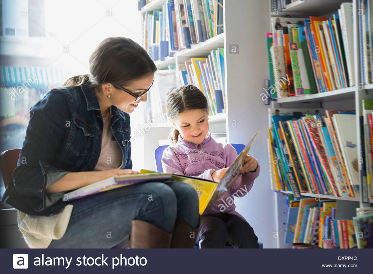 Mother and Daughter reading book in bookstore Photo Stock