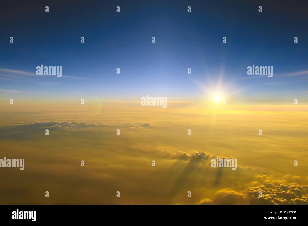 Vue spectaculaire sur le coucher du soleil au-dessus des nuages à partir de la fenêtre de l'avion Photo Stock