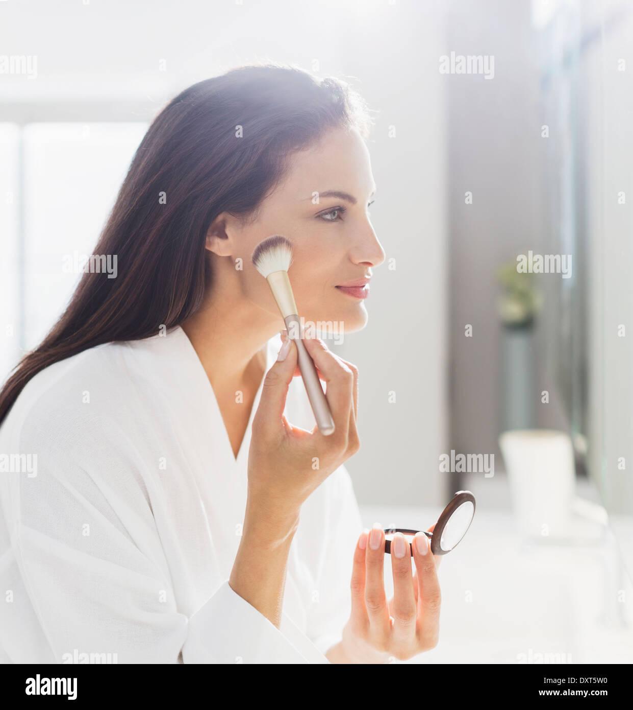 Femme en peignoir appliquant le maquillage dans la salle de bains Photo Stock