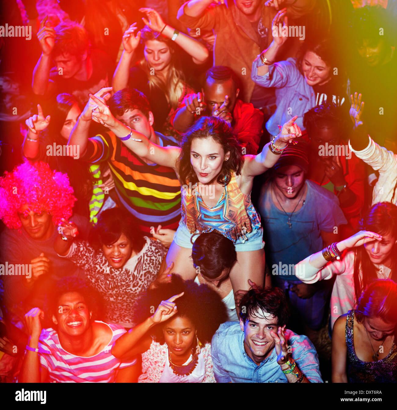 Cheering woman sur manÍs épaules à music festival Photo Stock