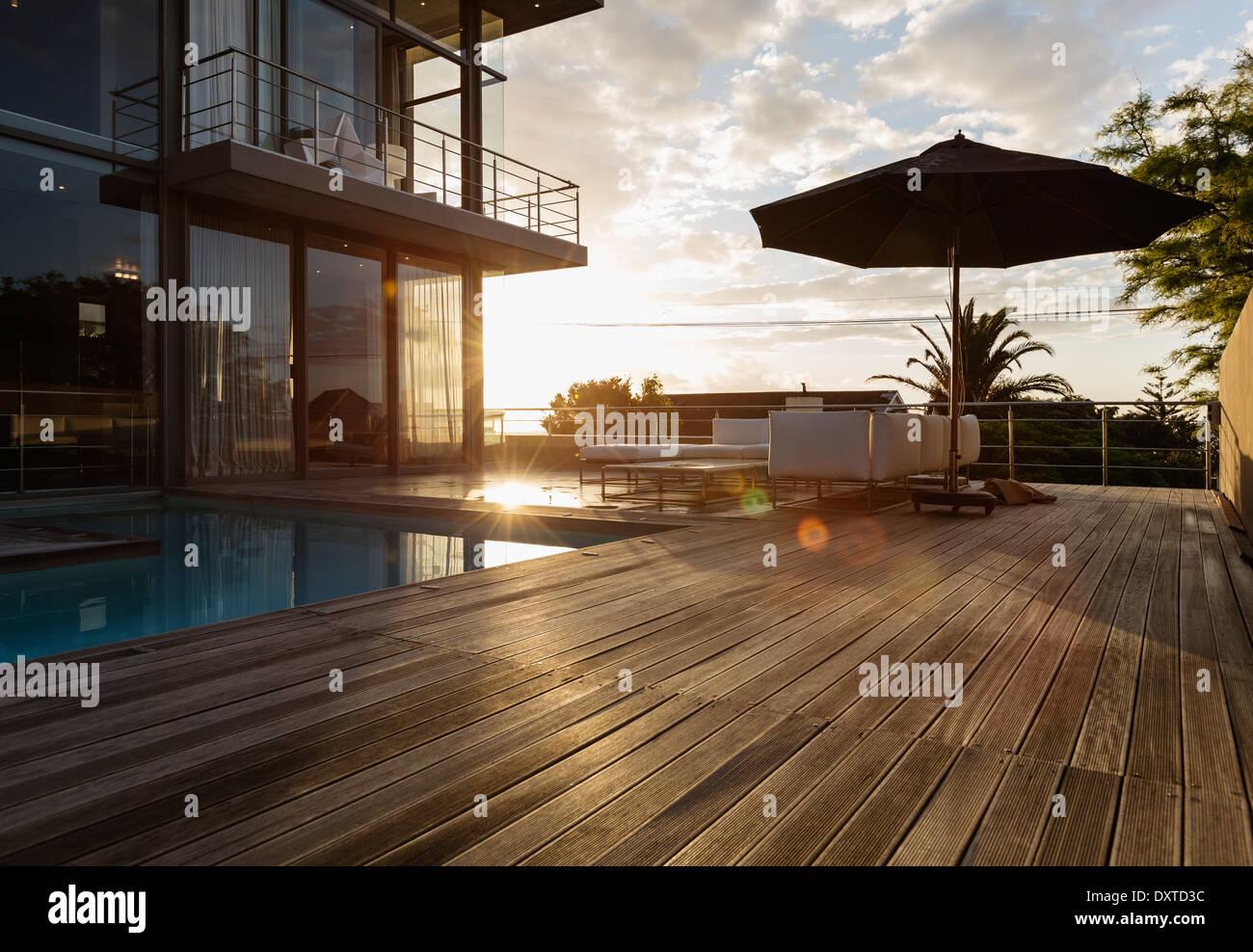 Soleil derrière maison de luxe avec piscine Photo Stock
