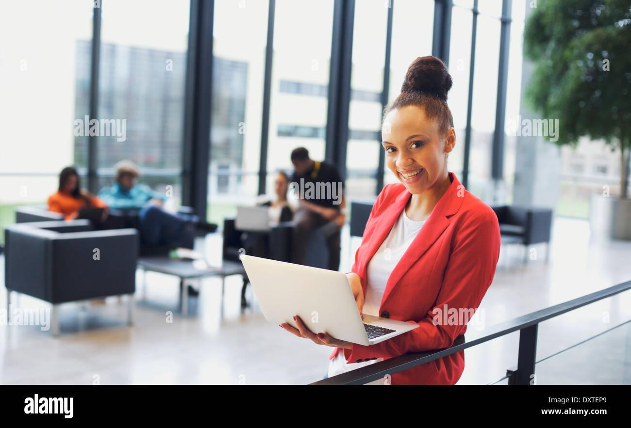 Belle jeune femme avec un ordinateur portable dans un bureau moderne. African American Woman par une balustrade avec les gens au travail. Banque D'Images